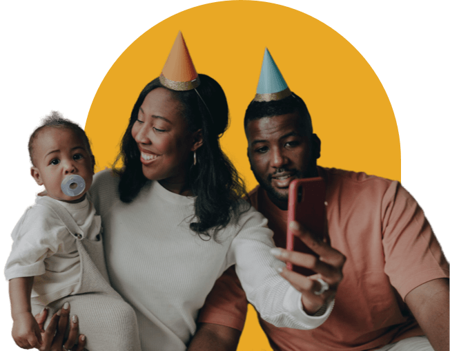 A child surrounded by its smiling parents on its first birthday.